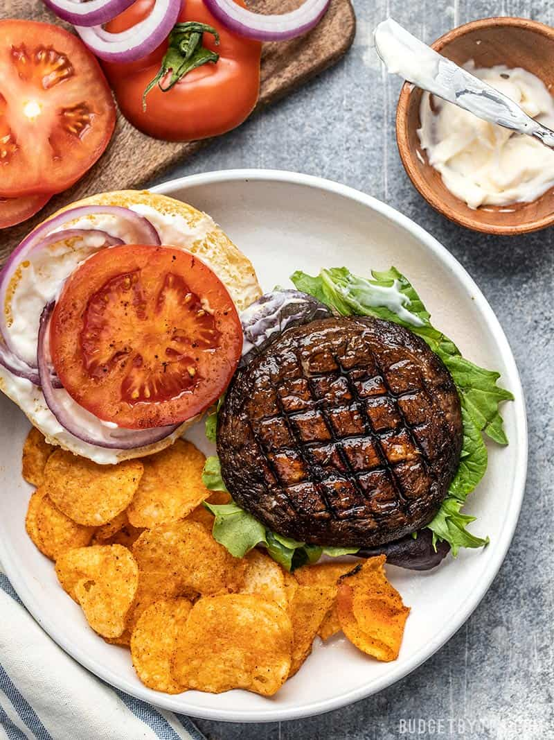 An open Marinated Portobello Mushroom Burger on a plate with chips, mayo, sliced tomato, and red onion rings on the side.