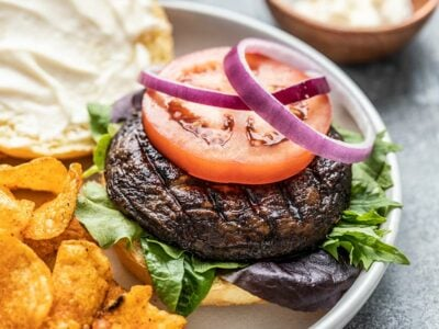 Close up side view of a marinated portobello mushroom burger topped with a slice of tomato and two red onion rings.