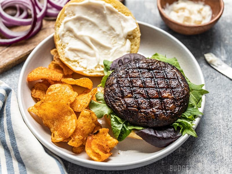An open marinated portobello mushroom burger on a plate with chips, viewed from the front.