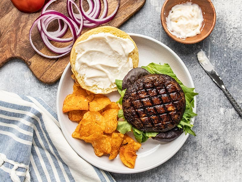 An open portobello mushroom burger on a plate with chips, a small dish of mayo and onion rings on the side.