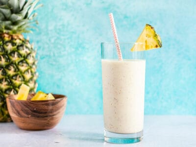 A pineapple protein smoothie in a tall glass with a paper straw, next to a whole pineapple and a small bowl of pineapple chunks