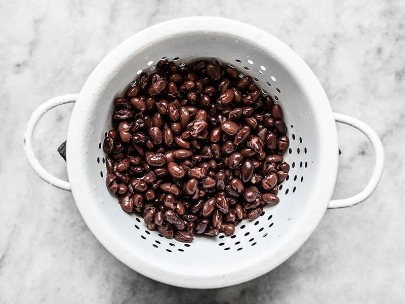 Rinsed and drained black beans in a white colander