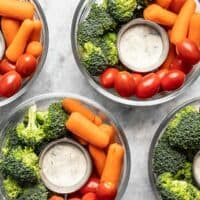 Four glass bowl veggie snack packs with ranch dressing, broccoli, and tomatoes.