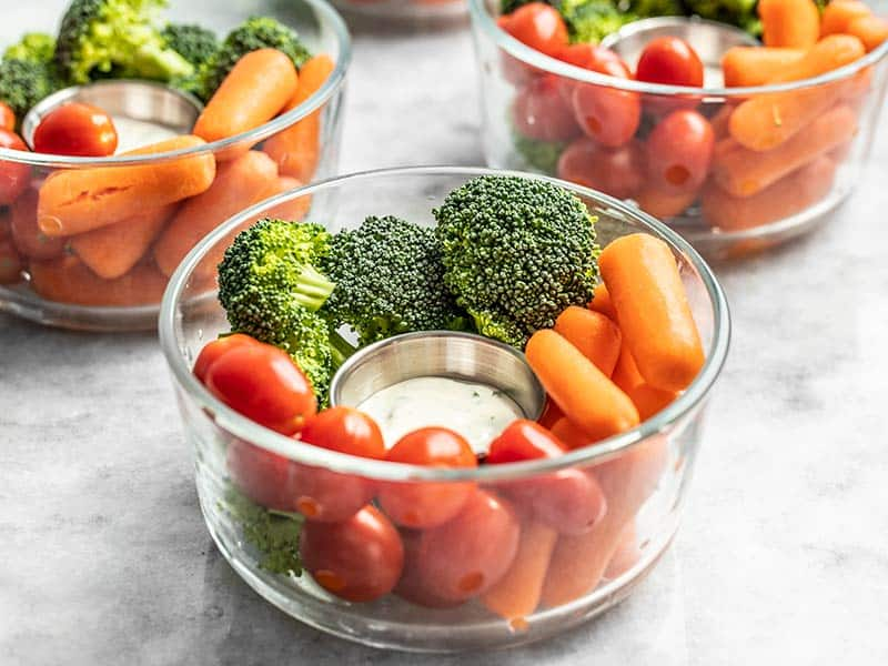 Front view of glass bowl veggie snack packs with ranch dressing, broccoli, carrots, and tomatoes.