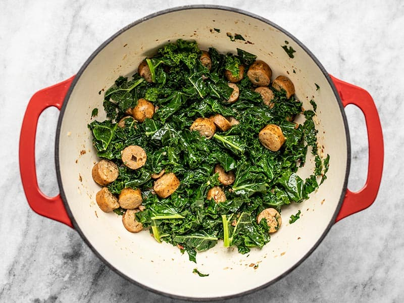 Wilted kale with chicken sausage in the pot.
