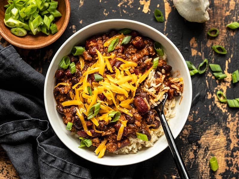 Overhead view of a bowl full of BBQ Beef and Beans, served with rice and topped with cheddar and green onion. A bowl of green onion on the side.