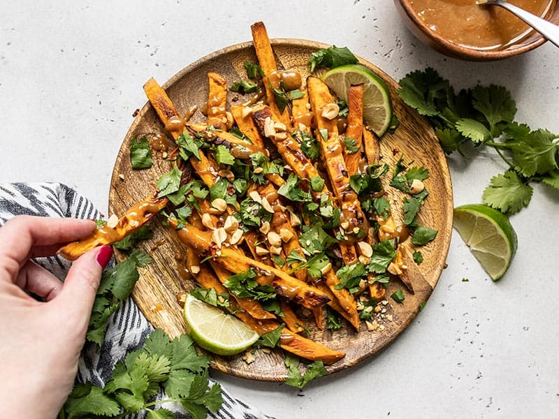 A plate full of baked sweet potato fries and peanut lime dressing, a hand sneaking one fry off the side.