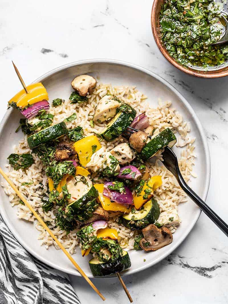 Chicken and vegetables removed from one chimichurri chicken kebab, on a bed of rice with a fork.