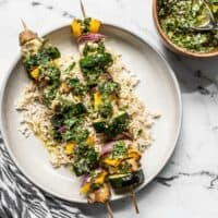 Two chimichurri chicken kebabs on a bed of brown rice, next to a bowl of chimichurri.