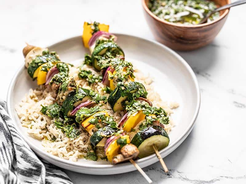 Front view of a plate with rice and two chimichurri chicken kebabs, with a wooden bowl of chimichurri in the back.