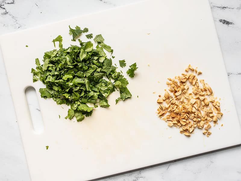 Chopped cilantro and peanuts on a cutting board.