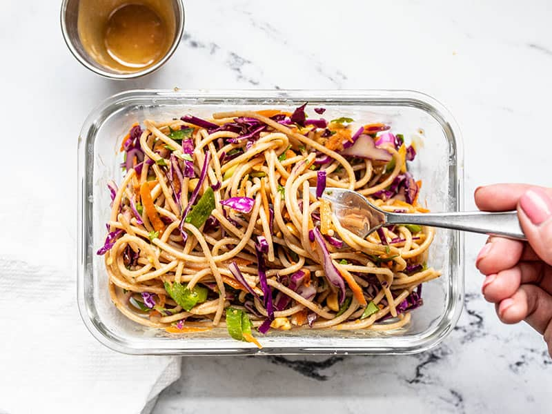 A meal prep container of Cold Peanut Noodle Salad being eaten with a fork, the empty dressing container on the side.