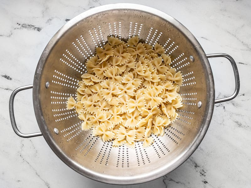 Cooked bowtie pasta draining in a colander.