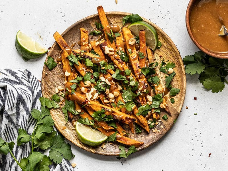 A wooden plate full of baked sweet potato fries drizzled with peanut lime dressing and topped with cilantro, peanuts, and red pepper.