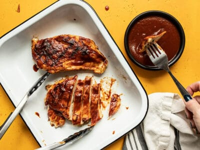 Two grilled chicken breasts coated in homemade bbq sauce in a dish, one sliced into strips, and a fork dipping a piece of chicken into a bowl of sauce.