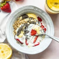 A half stirred Lemon Berry Yogurt Breakfast Bowl with a cut lemon and some strawberries near by.