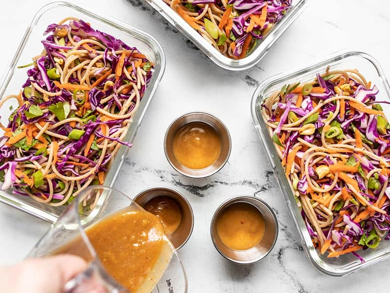 Cold Peanut Noodle Salad divided between meal prep containers, dressing being poured.