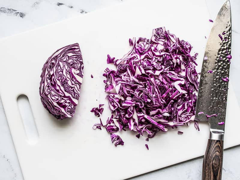Shredded red cabbage on a cutting board