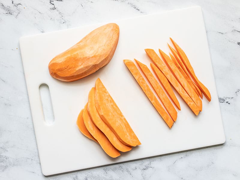 A peeled sweet potato being sliced into fries.