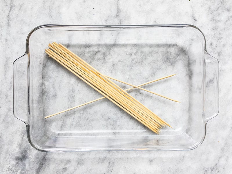 Wooden kebab skewers soaking in a dish of water