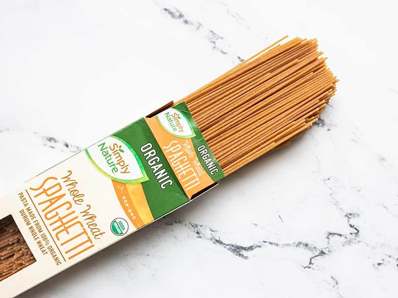 An open box of whole wheat spaghetti with the noodles coming out of the end.