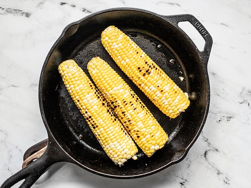 Charred corn cobs in a cast iron skillet