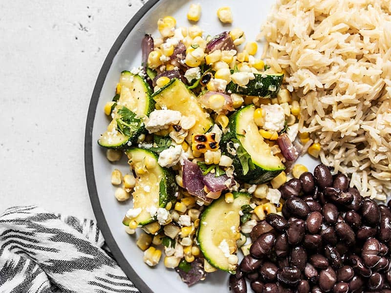 Close up of Charred Corn and Zucchini Salad on a plate with black beans and rice.
