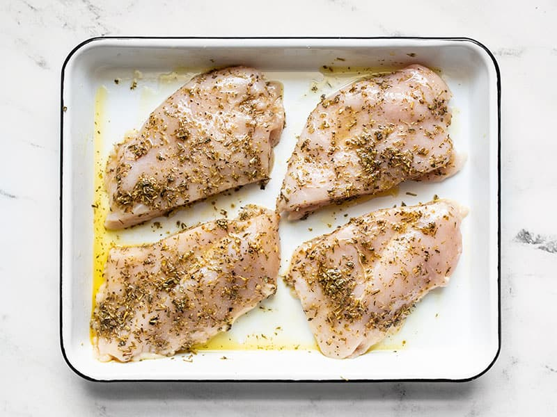 Chicken coated in herbs and oil in a baking dish.