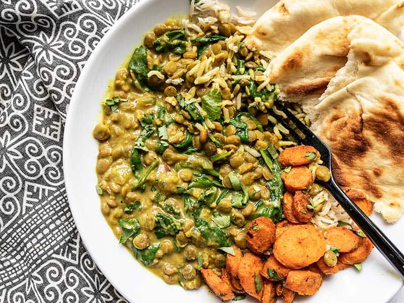 Creamy Coconut Curry Lentils with spinach on a plate with rice, naan, and curry roasted carrots.