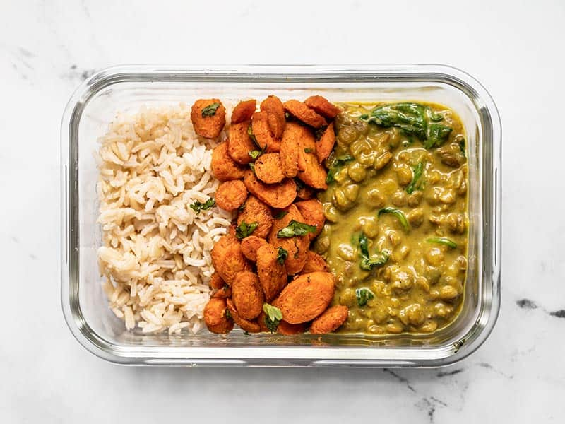 Creamy Coconut Curry Lentils in a glass meal prep container with rice and curry roasted carrots