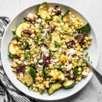 Overhead view of a bowl of Charred Corn and Zucchini Salad with a black and white napkin on the side.