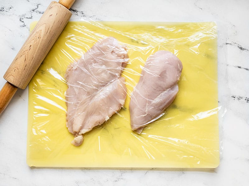 Chicken breasts on a cutting board covered with plastic with a rolling pin on the side.