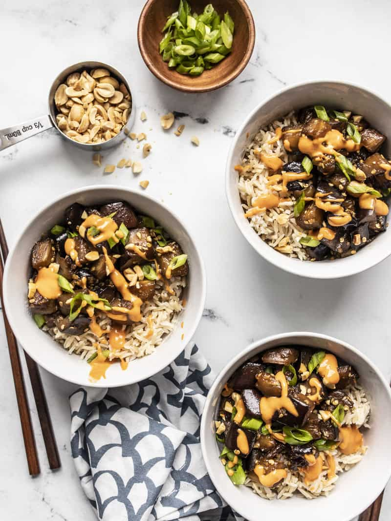 Overhead view of three bowls of Soy Glazed Eggplant served with rice, peanuts, and green onion