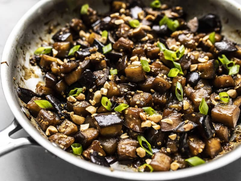 Close up side view of Soy Glazed Eggplant in the skillet, topped with peanuts and green onion