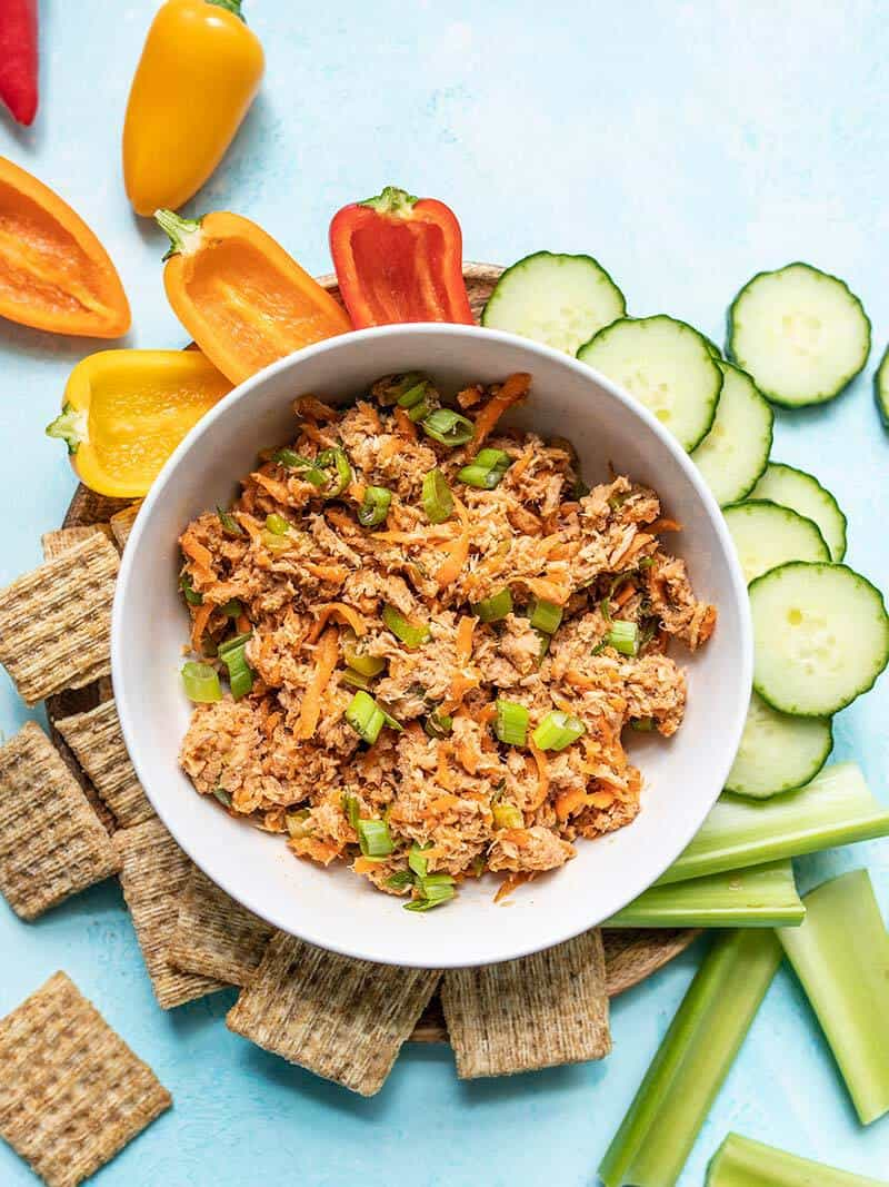 A bowl of Sweet and Spicy Tuna Salad surrounded by crackers and vegetables on a blue surface.