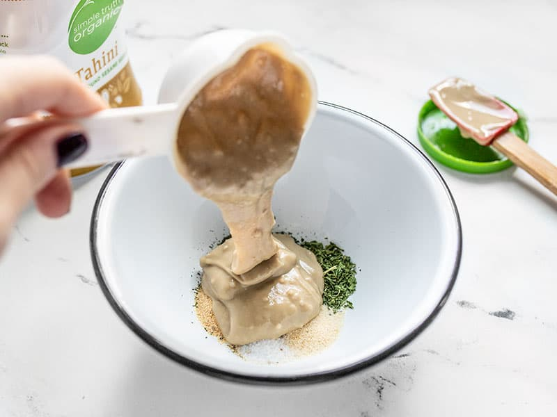Tahini being poured into bowl with the herbs.