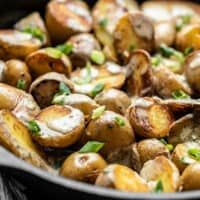 Close side view of a skillet full of potatoes topped with tahini dressing and green onion