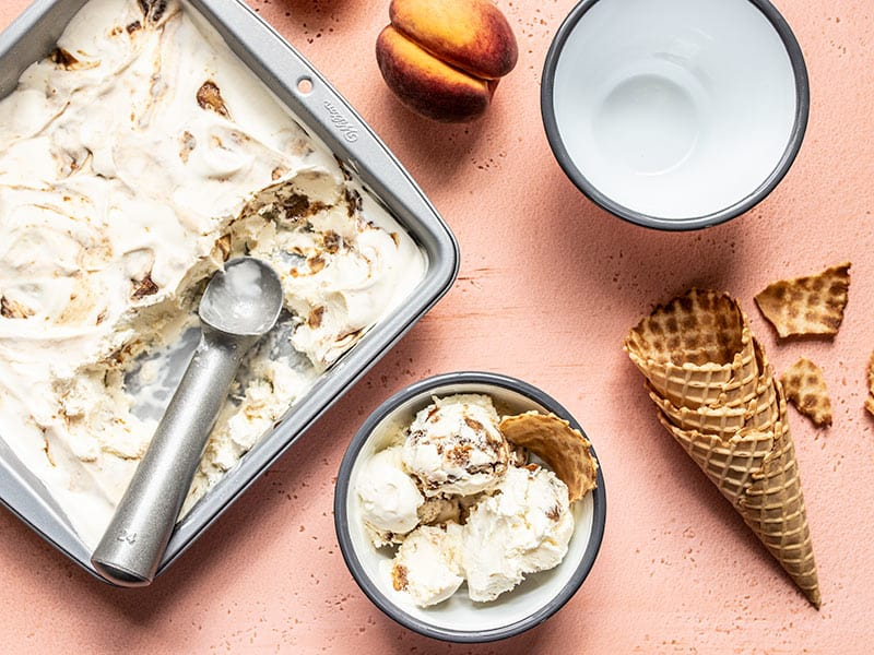 Baking pan full of No Churn Balsamic Peach Ice Cream scooped out and served in one bowl, with one empty bowl, and some waffle cones.