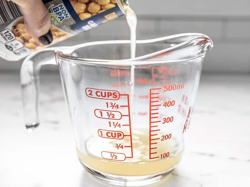 Pour aquafaba from the can of chickpeas into a measuring cup