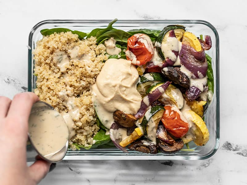 Dressing being poured onto a Roasted Vegetable Salad Meal Prep container