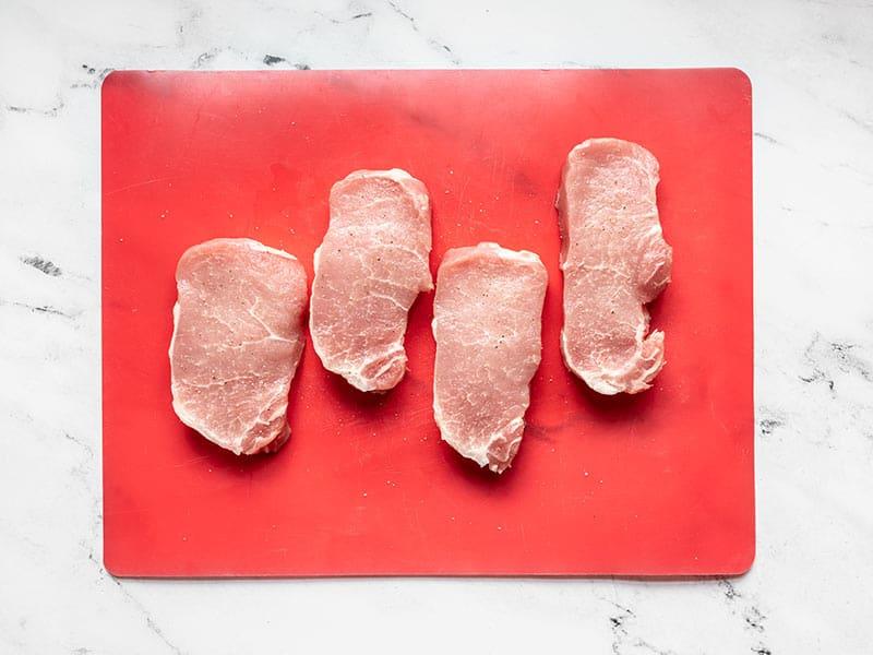 Season center cut pork chops with salt and pepper