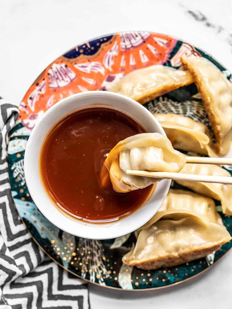 A dumpling being dipped into a bowl of Simple Sweet and Sour Sauce on a colorful plate.