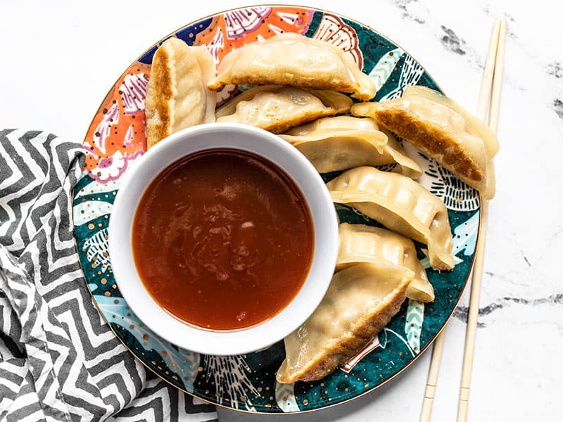 A bowl of Simple Sweet and Sour Sauce on a colorful plate with dumplings, chopsticks on the side.