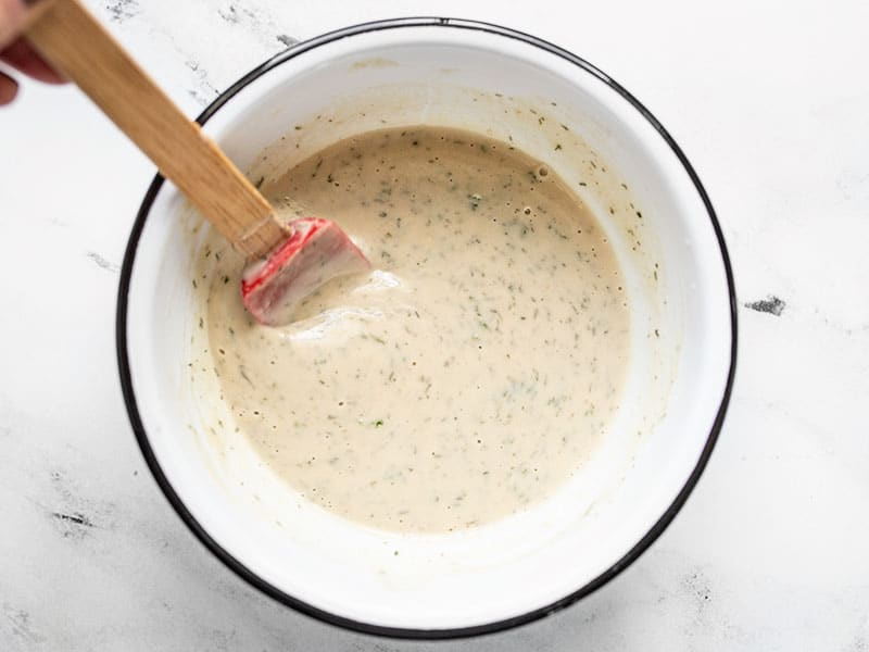 Lemon Dill Tahini Dressing in the bowl with a red spatula