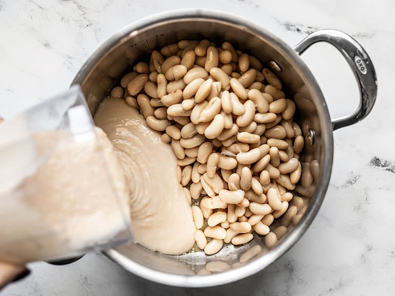 Add white beans (whole and pureed) to the soup pot