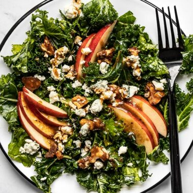 Close up overhead view of Autumn Kale and Apple Salad, with balsamic vinaigrette and a fork on the side.