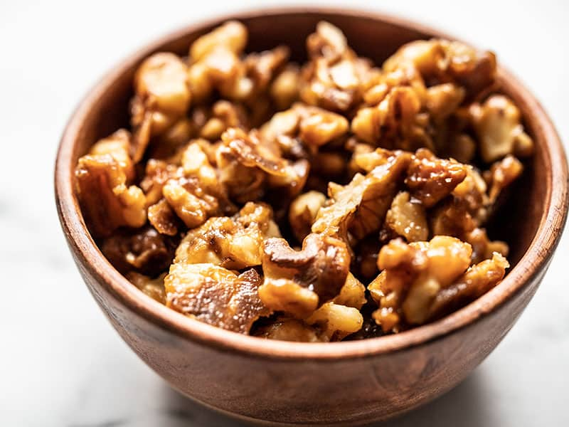 Close up of crunchy candied walnuts in a small wooden bowl