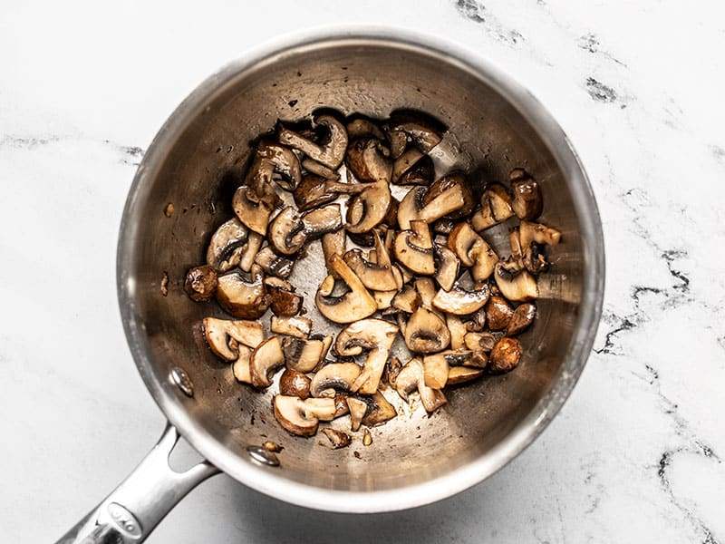 Cooked sliced mushrooms in a sauce pot