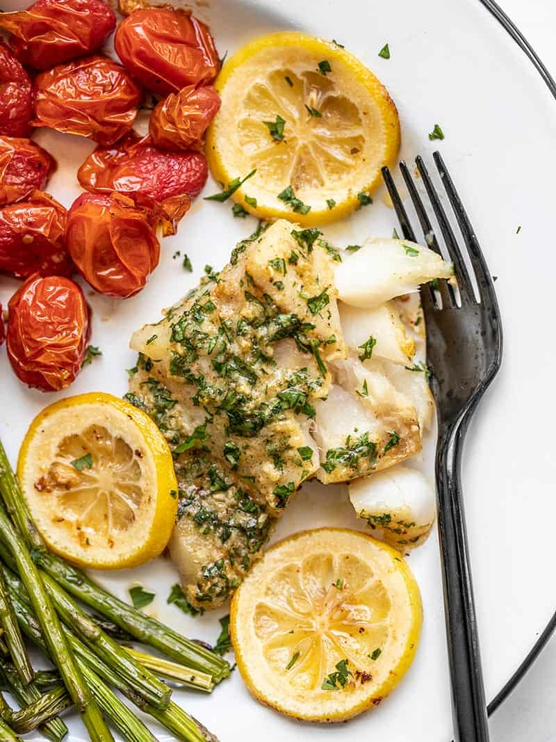 Garlic butter baked cod on a plate with tomatoes and asparagus, with a black fork on the side.