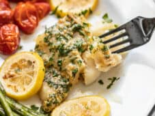 Close up of a fork digging into a filet of Garlic Butter Baked Cod on a plate with vegetables.